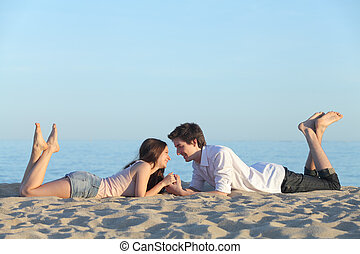 Couple dating and resting on the beach sand with the blue...