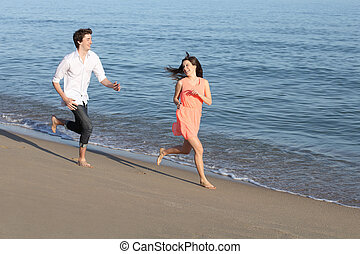 Couple of teenagers running and flirting on the beach
