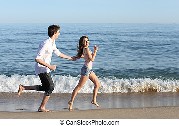 Couple chasing and running on the beach shore with the sea...
