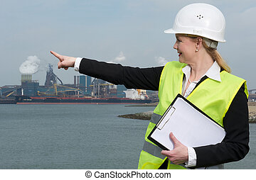 Female inspector in hardhat and safety vest pointing at...