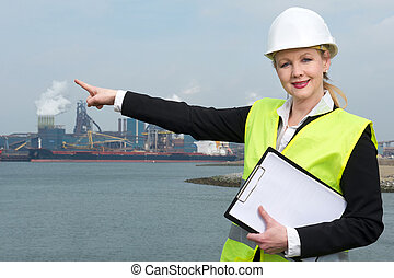 Female supervisor in hardhat and safety vest pointing to industrial site