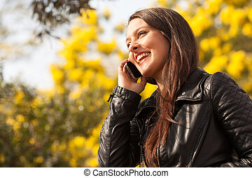 young latin woman using celphone outdoors