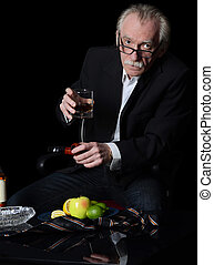The elderly man with a glass of whisky on black background -...