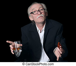 The elderly man with a glass of whisky on black background