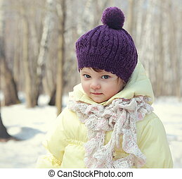 Happy baby girl in hat outdoor winter background