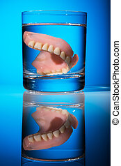 dentures in a water glass - a denture is cleaned in a glass...