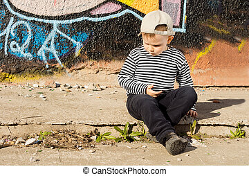 Pensive little boy sitting thinking as he sits on the...