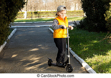 Young boy riding a scooter up a paved outdoor pathway in a...