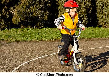 Cute young boy practising riding his bike - Cute young boy...