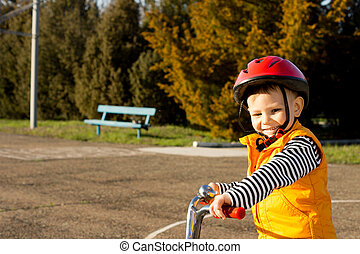 Happy small boy out riding his bicycle wearing a safety...