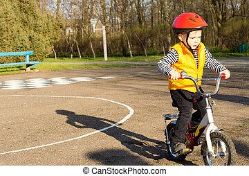 Little boy pedalling his bike - Cute little boy dressed in a...