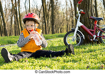 Young cyclist enjoying a drink of refreshing water from a...