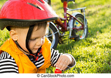Little boy out cycling drinking bottled water - Little boy...