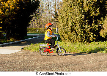 Cute little boy learning to ride pedalling his bicycle along...