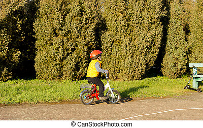 Active little boy riding his bike in the park - Active...