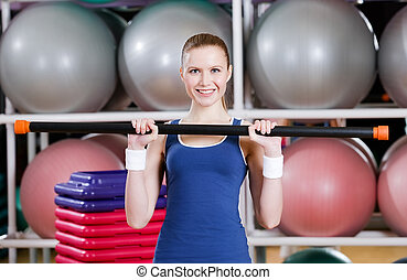 Athlete woman working out with gymnastic stick
