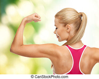 sporty woman showing her biceps - picture of young sporty...