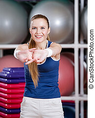 Woman stretching herself - Woman in sportswear stretching...