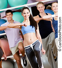 Group of people with perfect figures exercise at the gym in...