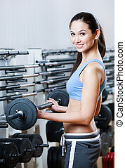 Sportive woman with dumbbells in sport centre