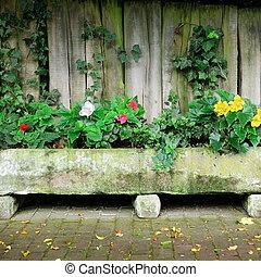Flower bed near board fence...