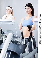 Two women training on simulators in gym
