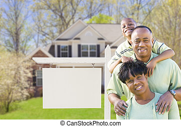 African American Family In Front of Blank Real Estate Sign...