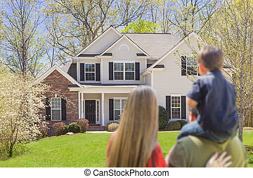 Mixed Race Young Family Looking At Beautiful Home - Mixed...
