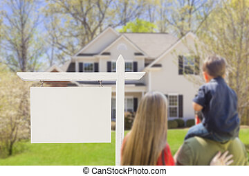 Family in Front of Blank Real Estate Sign and House