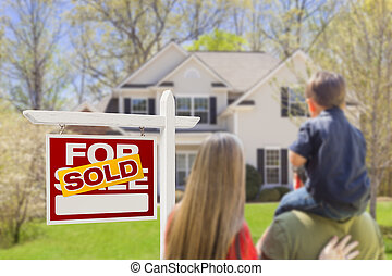Family Facing Sold For Sale Real Estate Sign and House -...