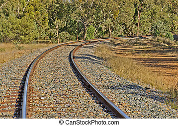 transport, - railway track curves through treesand around...