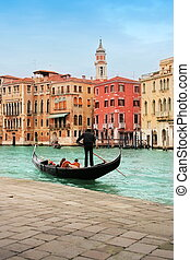 Venice: classic view of a romantic ride on a gondola boat in...