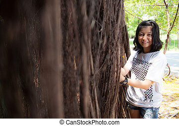 Young woman standing under a large tree.