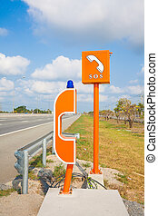 SOS sign and phone box on highway, road safety