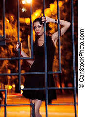 Pretty woman posing in cage outdoors at night