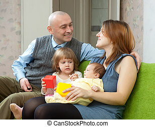 family of four with newborn baby