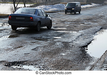 Road destroyed after winter in Ukraine. Puddles in the pits...