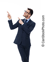 Smiling young businessman pointing at copy space