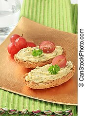 Whole grain crisp rolls with herb butter and grapes
