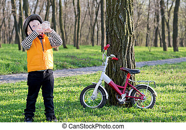 Young sportsman stopping for a drink - Young boy dressed in...
