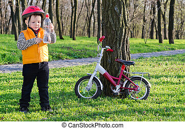 Young rider checking his bottled water - Young little boy...