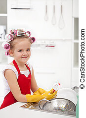 Little girl with big curls doing the dishes - smiling,...