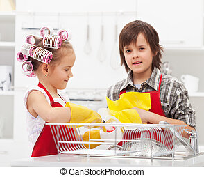Kids doing the dishes together in the kitchen - closeup on...