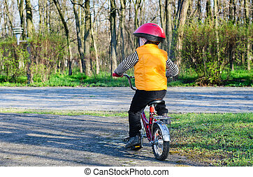 Little boy riding away from the viewer - Little boy in a...