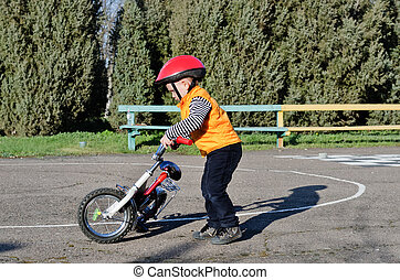 Little boy playing with his bike outdoors dressed in a...