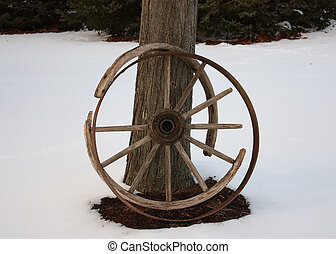 Old Wagon Wheel - An old broken wagon wheel in the snow.