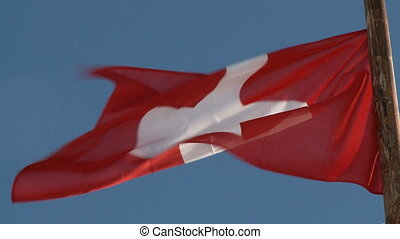 Flag of Switzerland in front of blue sky
