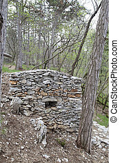 Herdsman stone house in the wood, shelter from the rain