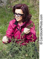 Smiling woman picking wild asparagu