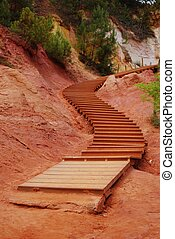 Ocher walk stairs - The red ocher walk with wooden stairs in...